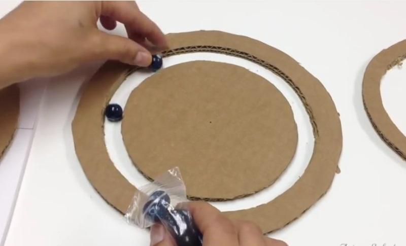 elle met des billes entre deux cercles de carton sa cr ation est tr s pratique pour les. Black Bedroom Furniture Sets. Home Design Ideas
